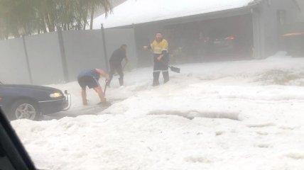 Спасатель помогает жителям расчищать подъездную дорожку.